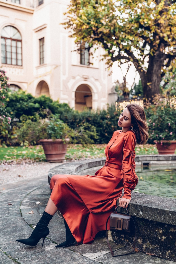 """The """"it"""" hue of the season - burnt orange - wearing a Jonathan Simkhai dress in the shade with Balenciaga black sock booties and Boyy bag while in the gardens at Four Seasons Florence  #eveningdress #sockbooties #outfitidea #stylingtips #fashionblogger #ContributingEditor"""